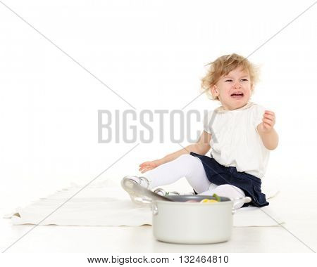 Unhappy crying little child sits on the floor on a white background.