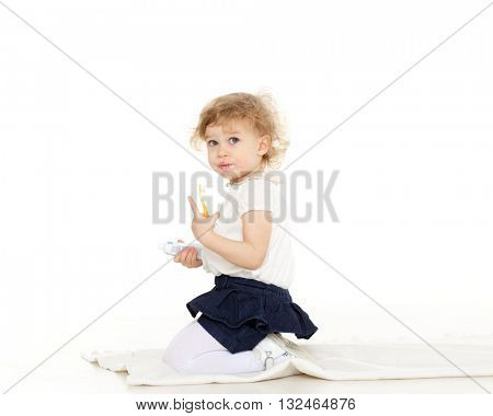 Little pretty girl sits on the floor with toothbrush and paste on a white background.