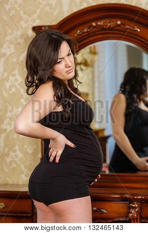 Pregnant woman feeling strong  pain in her back in the room of the house.