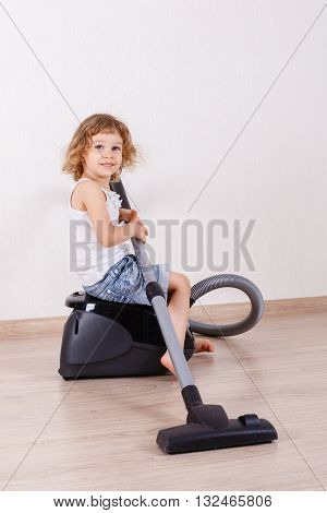 Little girl cleans the floor in the room with a vacuum cleaner.  Mother's helper. Housekeeping.