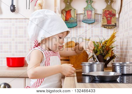 Little girl in apron and cap of the cook stands in the kitchen near cooker in the house. Mother's helper. 2 year old.