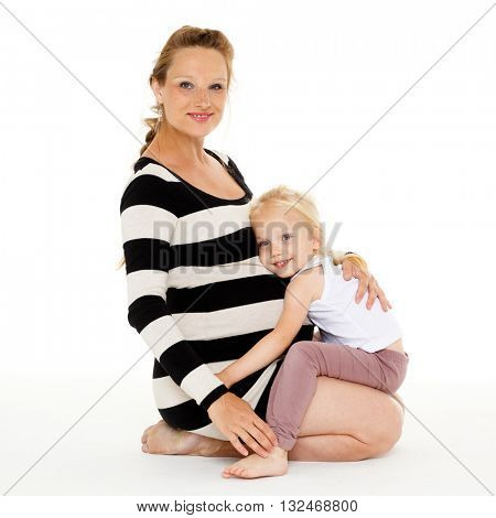 Little girl embracing pregnant mother on a white background. Happy family.