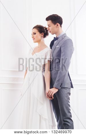 Gorgeous bride in white dress and handsome groom in grey tuxedo posing in retro interior.