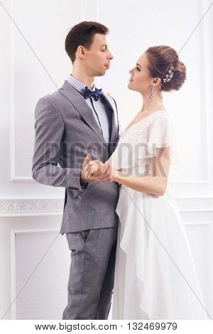 Beautiful bride in white dress and handsome groom in grey tuxedo dancing in retro interior.
