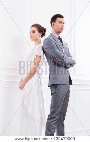 Beautiful bride in white dress and handsome groom in grey tuxedo posing in retro interior.