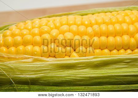 One ear of corn ripe on a wooden surface