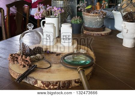 salt and pepper in white bottle as seasoning on wooden table in restaurant with decoration with seasoning