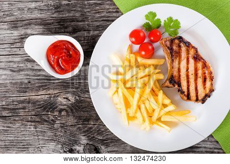 grilled pork chops on a white dish with french fries cherry tomatoes cilantro leaves and ketchup on a wooden table blank space left top view