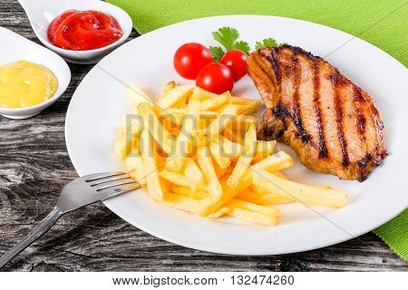 grilled pork chops on a white dish with french fries cherry tomatoes cilantro leaves mustard and ketchup on a wooden table close-up