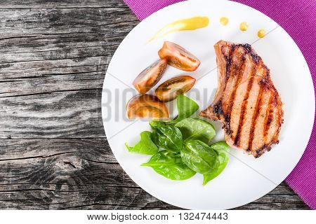 grilled pork chops on a white dish with slices of black tomatoes spinach leaves on a table mat on a wooden tabl top view