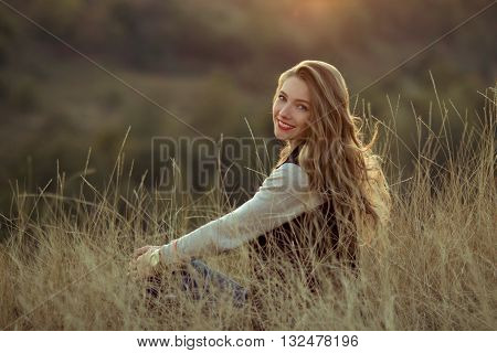 Happy, cheerful, joyful, smiling girl sitting on the hill with very incredibly, beautiful view, watch sunset. Beautiful girl sitting outdoor, in mountains, sunlight, sunny field. Attractive girl with nice smile