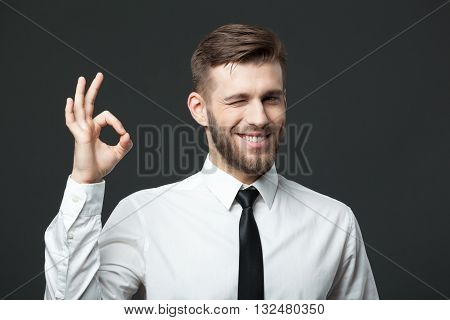 Handsome Businessman Showing Okay Sign On Dark Gray Background.