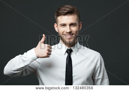 Handsome Businessman Showing Thumbs Up Sign On Dark Gray Background.