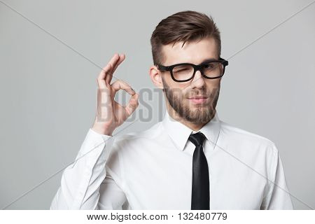 Handsome Businessman Showing Okay Sign On Gray Background.