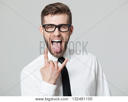 Handsome Businessman Showing Goat Gesture And His Tongue Isolated.