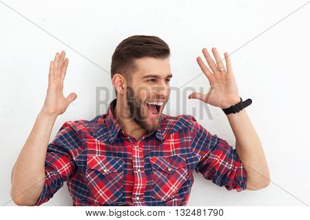 Portrait Of Happy Surprised Handsome Young Man Against White Wall.
