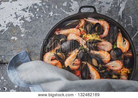 Paella in the pan on the metal background top view