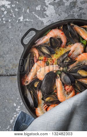 Paella in the pan on the metal background vertical