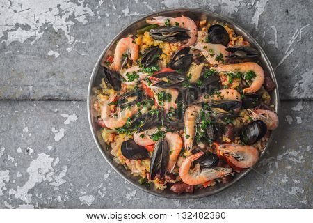 Paella in the metal plate on the metal background top view
