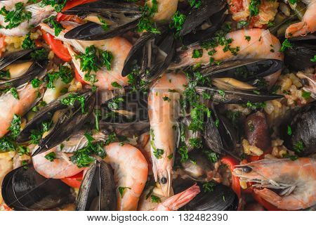 Paella with seafood and greens background close-up