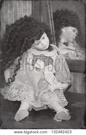 Creepy distressed photo of a doll looking into a mirror.