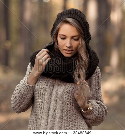 Lovely closeup portrait of gorgeous, sensual, elegant girl outdoors, in sunny autumn forest, sunlight. Beautiful, attractive, awesome, pretty girl in beige, brown sweater, black hat, black scarf, light skin, face