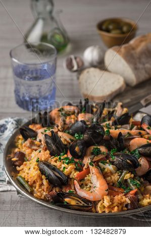 Paella in the metal plate on the wooden table vertical