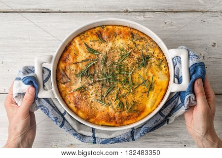 Moussaka with rosemary in the ceramic pan in the hand top view
