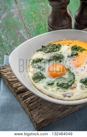 Florentine eggs with pureed spinach on the wooden table vertical