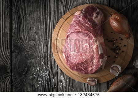 Raw angus beef with seasoning on the wooden table top view