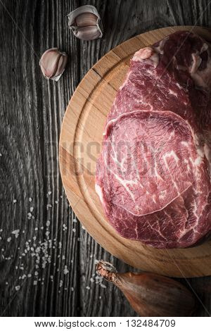 Raw angus beef with seasoning on the wooden table vertical