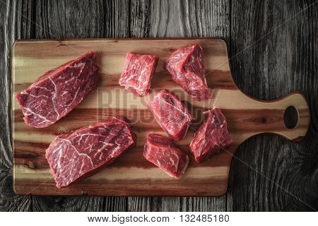 Raw angus beef slices on the wooden board top view