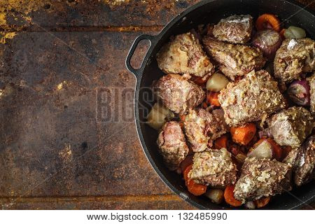 Meat with vegetables in the pan on the metal background