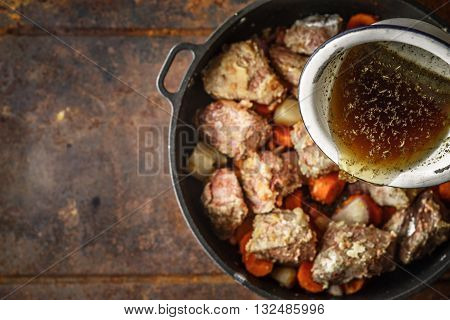Adding broth in the pan with meat and vegetable top view