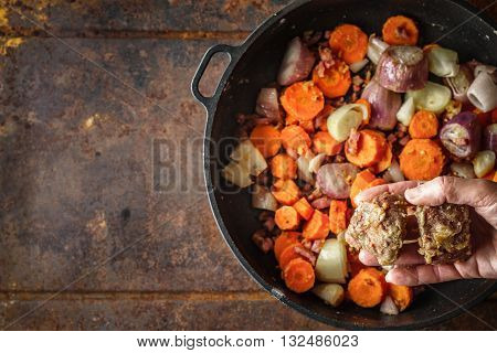 Adding fried meat in the pan with carrots and shallot top view