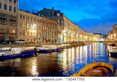 SAINT-PETERSBURG, RUSSIA - APRIL 21, 2016: Excursion boats on the Moika River near The Nevsky Avenue and The Green Bridge. On the background is The Pevchesky Bridge. Night view.