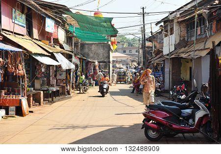 GOKARNA KARNATAKA INDIA - JANUARY 29 2016: A man wearing orange shawl at his head walking along street  in Gokarna city