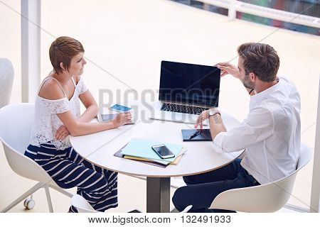 Business meeting between mixed gender partners seated at a round table, with man busy opening his ultrabook and woman busy paying close attention to his presentation.