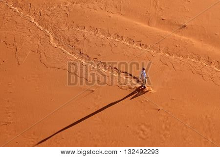 SOSSUSVLEI NAMIBIA - JAN 29 2016: Unidentified man descends from the high sand dune in the Namib desert at sunrise