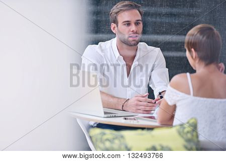 Interview between accomplished male businessman and a potential new female employee who appears to be a promising candidate for the role in question, as he questions her thoroughly.