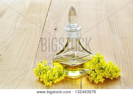 Rapeseed oil with rape flowers over wooden table
