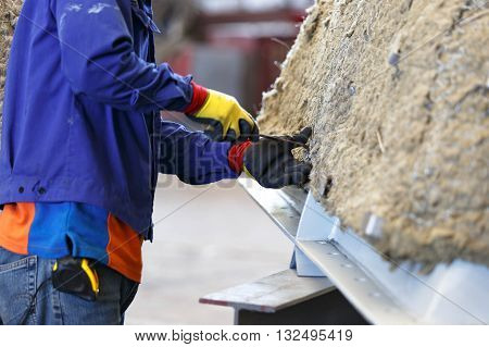 Worker is bending pin to lock insulation on surface