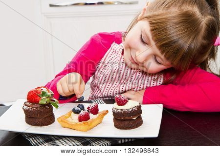 little girl preparing and eating cake with fruit