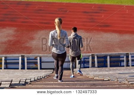 fitness, sport, exercising and lifestyle concept - couple walking downstairs on stadium