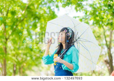 Beautiful Asian Young Woman With Green Dress Blowing Bubble In Park