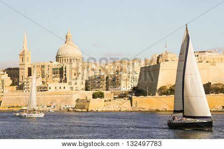 Panoramic view of Valleta harbor with sailing boats and Fort Saint Angelo