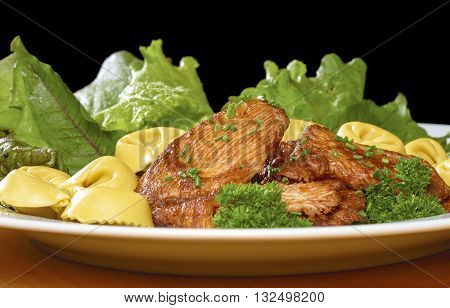 low angle shot of a roasted chicken dish with fresh green salad and tortellini noodles on a white plate in front of black back