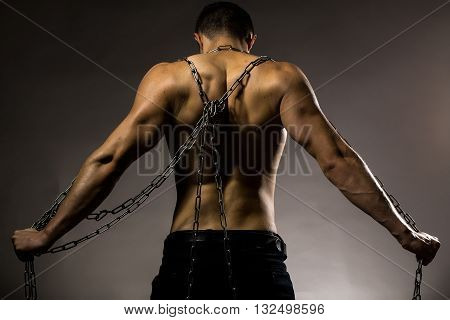 Young handsome man standing with chain on bare back and muscular body posing in studio on grey background