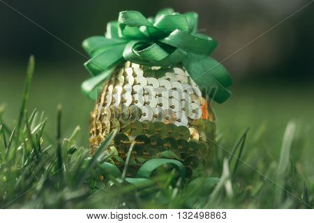 Easter egg decorated with golden sequins and green ribbons on blurred grass background