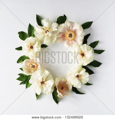 floral wreath frame with white peony flowers and green leaves on white background. Flat lay top view